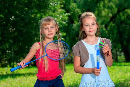 jugando tenis: Dos niñas felices jugando al aire libre de tenis. Foto de archivo