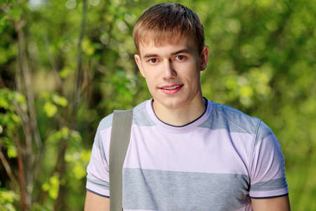 Portrait of a young man student outdoors. photo