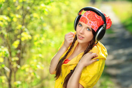 Portrait of cute summer girl listening to music outdoor.  photo