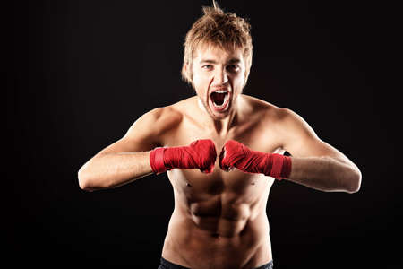 Portrait of an aggressive boxer in red gloves posing at studio. photo