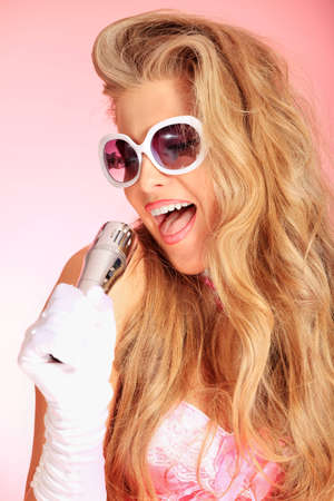 Portrait of a charming blonde woman singing with microphone in studio over pink background. photo