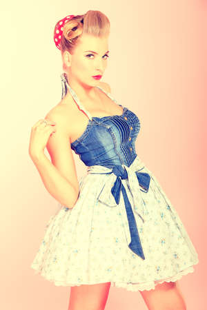50s adult: Beautiful young woman with pin-up make-up and hairstyle posing over pink background. Stock Photo
