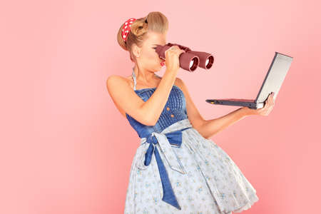 pinup: Attractive pin-up girl looking through binoculars to her laptop.
