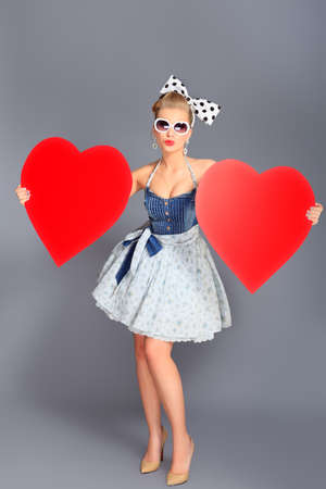 Beautiful young woman with pin-up make-up and hairstyle posing in studio with red hearts. photo