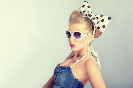 divas: Hermosa mujer joven con pin-up maquillaje y peinado posando en estudio.