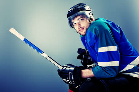 icehockey: Portrait of a handsome ice-hockey player with hockey stick. Studio shot.