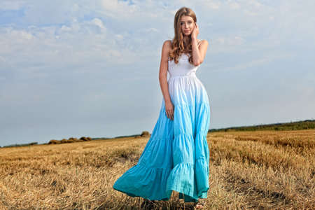hay field: Romantic young woman posing outdoor. Stock Photo