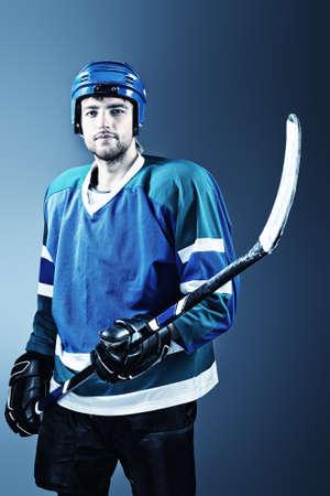 hockey sobre hielo: Retrato de un apuesto jugador de hockey sobre hielo con el palo de hockey. Estudio de disparo.
