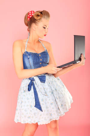 Smart pin-up girl posing over pink background with a laptop. photo