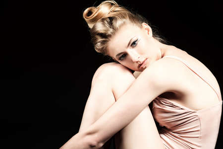 woman black background: Beautiful ballet dancer posing at studio. Stock Photo