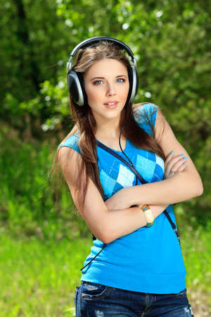 Portrait of cute summer girl listening to music outdoor. Stock Photo - 13832184