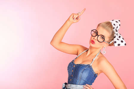 Beautiful young woman with pin-up make-up and hairstyle posing over pink background. photo