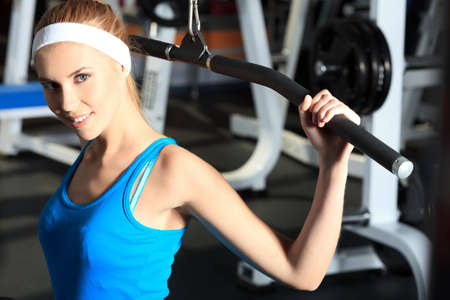 Young sporty woman doing exercises in the gym centre. Stock Photo - 13890372
