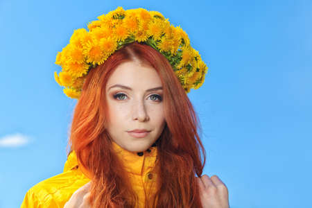 circlet: Beautiful young woman in a circlet of flowers over blue sky. Stock Photo
