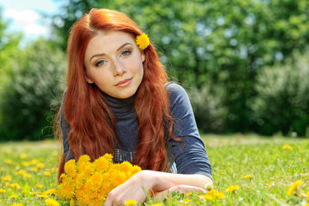 circlet: Romantic young woman in a circlet of flowers outdoors. Stock Photo