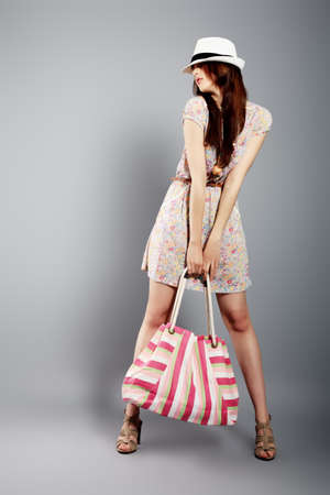 fashion bag: Shot of a beautiful girl in summer style posing at studio  Stock Photo