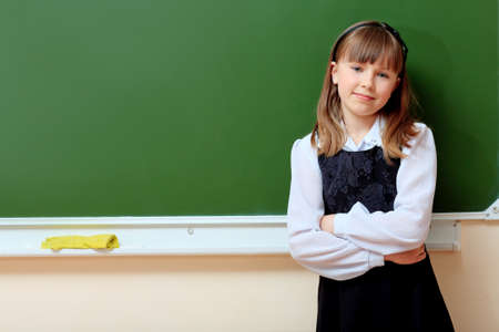 Portrait of a smiling schoolgirl in a classroom. photo
