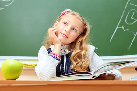 Portrait of a cute dreaming schoolgirl in a classroom. photo