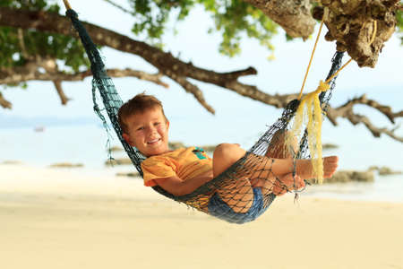 Cheerful little boy playing on a beach. Tropical getaway. photo