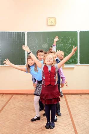classmates: Happy schoolchildren at a classroom. Education. Stock Photo