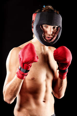 boxing equipment: Portrait of a handsome boxer in red gloves and helmet  posing at studio. Stock Photo