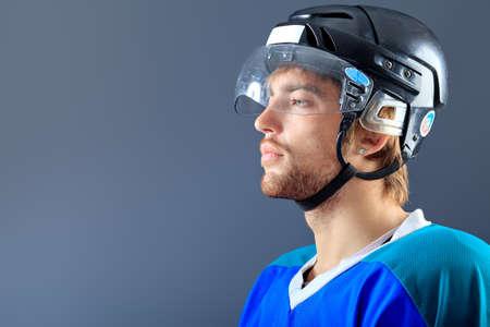 hockey ice: Portrait of a handsome ice-hockey player. Studio shot.