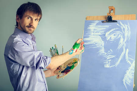 Portrait of an artist painting on easel. Shot in a studio. photo