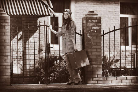 Beautiful young woman with old suitcase walking down the street. photo