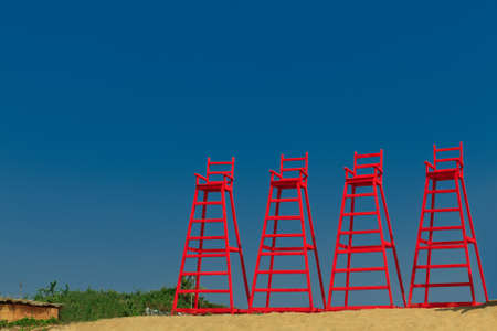 lifeguard tower: Several lifeguards towers on a tropical beach.