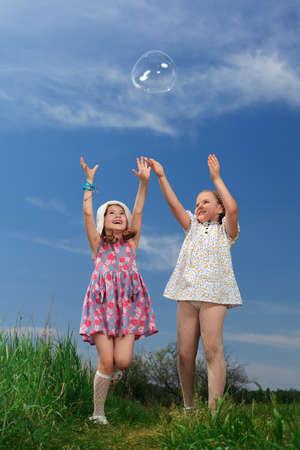 schulm�dchen: Zwei gl�ckliche M�dchen spielen mit gro�en Blasen in einem Park.