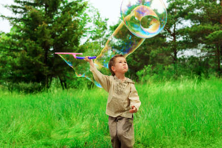 Portrait of a cute little boy playing with big bubbles outdoor. photo