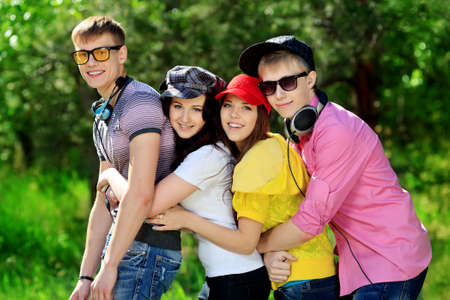teenagers laughing: Group of young people having a rest together outdoors. Stock Photo