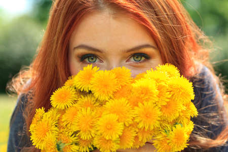 Portrait of a romantic young woman with a bouquet of dandelions outdoors. photo