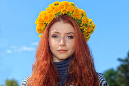 circlet: Portrait of a romantic young woman in a circlet of flowers outdoors.