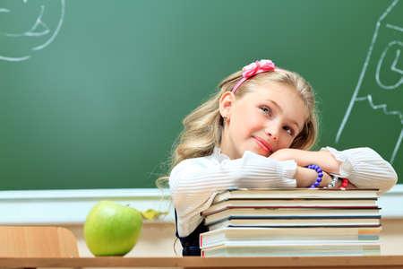 school life: Portrait of a cute dreaming schoolgirl in a classroom.