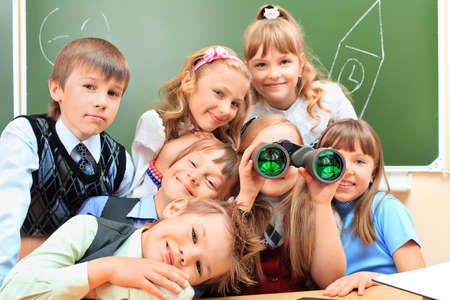 Happy schoolchildren at a classroom looking through binoculars. Education. Stock Photo - 14052340