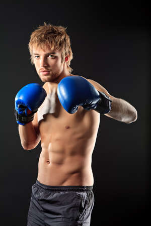 Portrait of an aggressive boxer in blue gloves posing at studio. photo