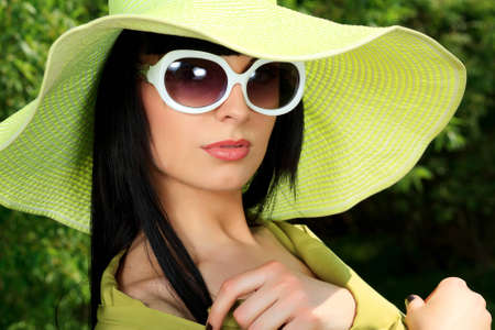 Portrait of a beautiful young woman in sunglasses posing outdoor. photo