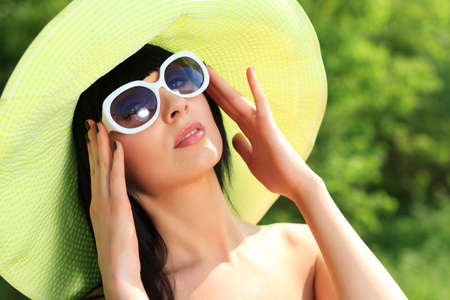 hot spring: Portrait of a beautiful young woman in sunglasses posing outdoor. Stock Photo
