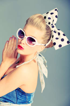 50s adult: Beautiful young woman with pin-up make-up and hairstyle posing in studio.