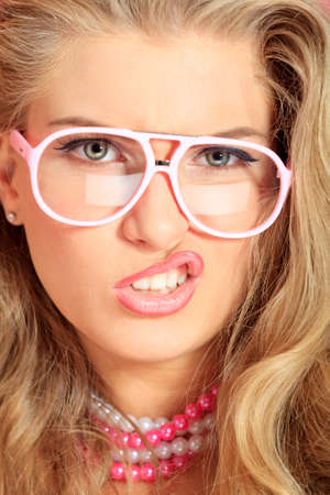 temptative: Portrait of an expressive blonde woman in pink spectacles posing in studio.