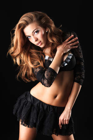 black cheerleader: Beautiful girl cheerleader posing at studio. Black background.