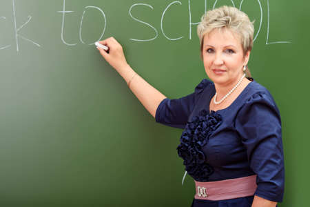 Portrait of a smiling teacher writing on a blackboard. photo