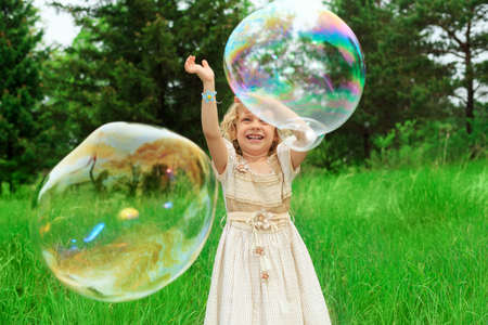 Pretty little girl is playing with big bubbles in a park. photo