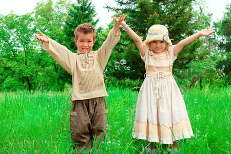 Happy little boy and girl having fun together outdoors. photo