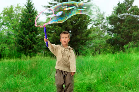 Cute little boy is playing with big bubbles outdoor. photo