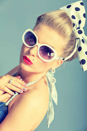 retro fashion: Beautiful young woman with pin-up make-up and hairstyle posing in studio.