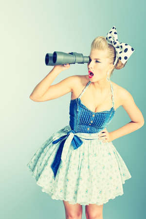 Beautiful young woman with pin-up make-up and hairstyle looking through binoculars. photo