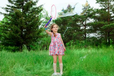 colegiala: Feliz niña está jugando con burbujas de gran tamaño en un parque.