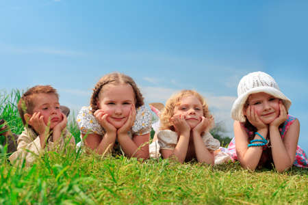 lying on grass: Group of happy children having a rest together outdoors. Stock Photo